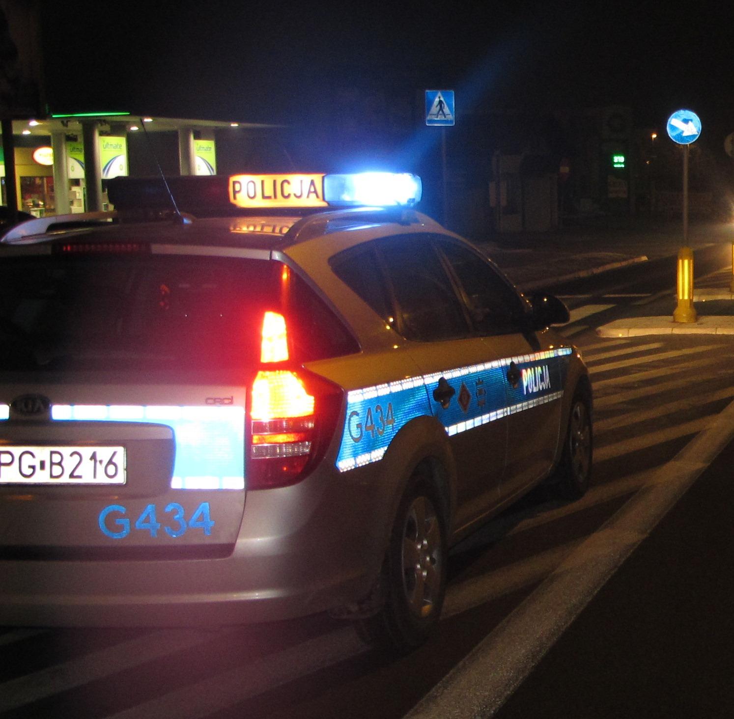 KPP Oświęcim radiowóz jadący ulicą na sygnałach w nocy