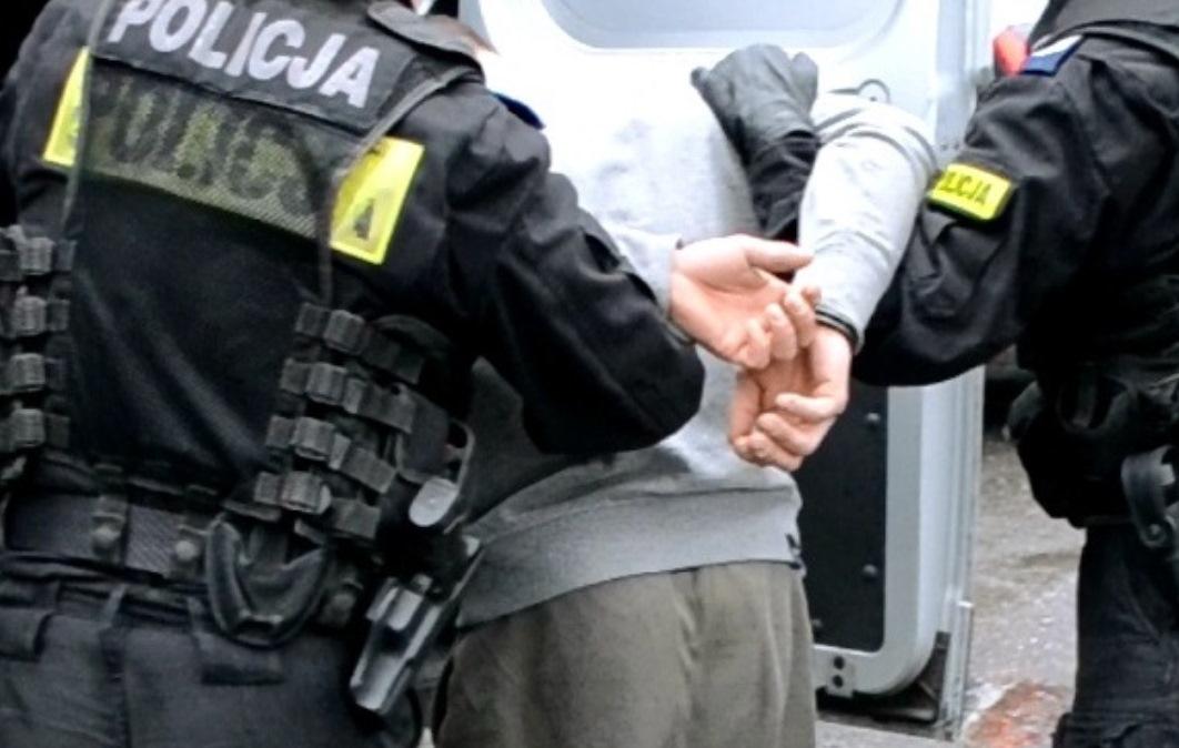 KPP Oświęcim policjanci doprowadzają zatrzymanego do radiowozu